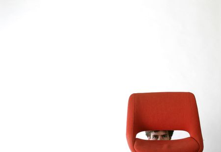 Shy man hiding behind a red chair. Stock Photo - 261031