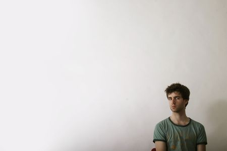 A male sitting alone in the corner of the image Stock Photo - 261034