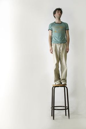 A male standing on a chair with a white background Stock Photo - 261033
