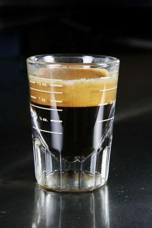 Single espresso in a shot glass with full crema photo