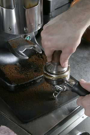 tamper: Detail image of tamping espresso grounds into a bayonet