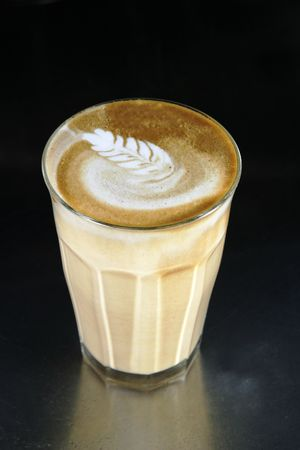 capucinno: A double latte in a tall latte glass with latte art Stock Photo