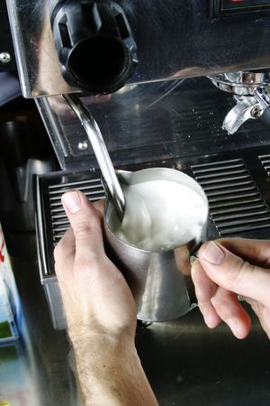 capucinno: A professional barista is steaming milk for a cafe latte