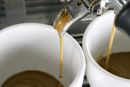Detail image of two cups of espresso being made in an industrial profesional machine Stock Photo