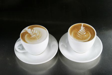 capucinno: Two single cappuccinos sitting ready with latte art Stock Photo