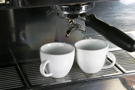 cortado: Two white cups waiting under an espresso machine ready Stock Photo