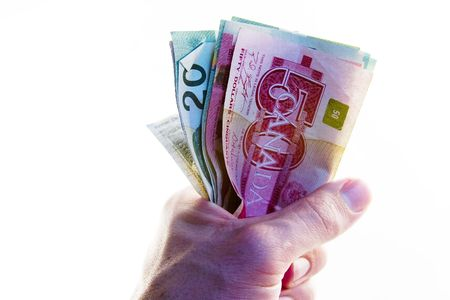 canadian cash: A male hand holding a tight wad of Canadian money.