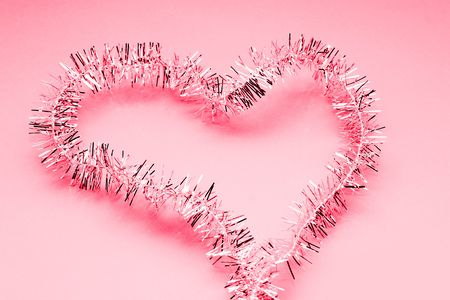 shiney: Tinsel in the shape of a heart with a red glow. Stock Photo