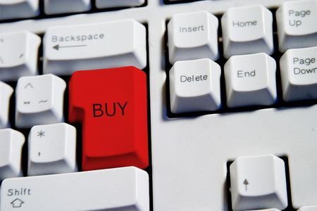 Computer Keyboard from a desktop computer with the enter key highlighted in Red with the word buy photo