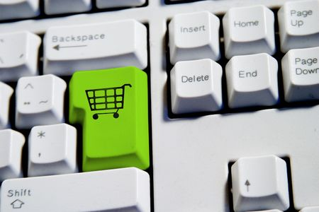 Computer Keyboard from a desktop computer with the enter key highlighted in green with a large shopping cart on it photo