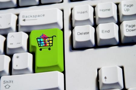 dar un regalo: Carrito de la compra lleno de regalos en un teclado de computadora.  Foto de archivo