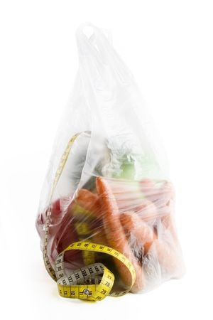 Healthy vegetables in a clear plastic grocery bag on a white background with a tape measure in the foreground photo