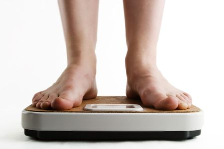 A pair of female feet standing on a bathroom scale Stock Photo - 280491