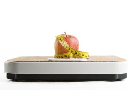 nourishment: An apple on a bathroom scale with tape measure.