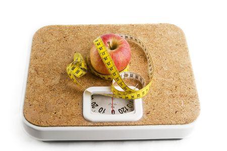 Una manzana en una balanza de ba�o con cinta m�trica.  Foto de archivo - 280419