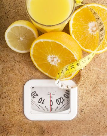 kilo: Fresh fruit juice on a bathroom scale. Stock Photo