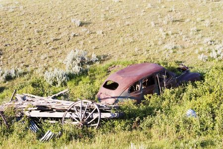 An old car sitting on the prairie forgotten and overgrown with bushes. photo