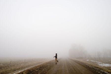 apparition: Walking alone on a saskatchewan road in the fog with a skip of joy Stock Photo