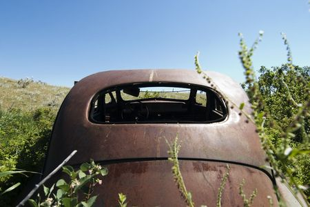 An old rusted out car on the prairie landscape photo