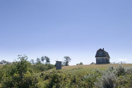 outhouse: An old prairie house on a grass meadow in Saskatchewan with an outhouse