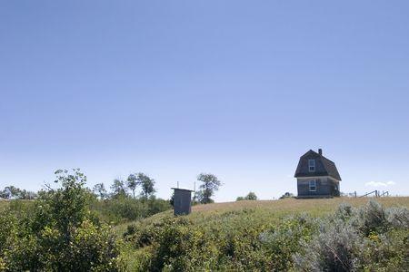 latrina: Una vecchia casa prateria su un prato in erba con una Saskatchewan outhouse  Archivio Fotografico