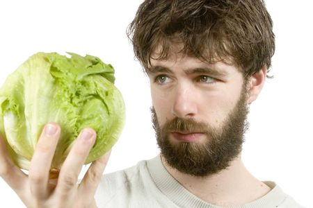 sceptic: A young male with a beard looking at salad with scepticism.  The salad is out of focus.