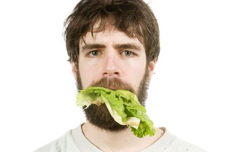 unimpressed: A young male with lettuce in his mouth, looking unimpressed.