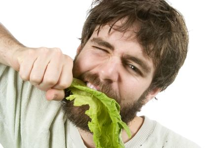 A young male with a beard is eagerly eating salad, as if he were a barbarian eating meat. photo