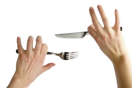 norm: Two awkward womans hands holding a knife and fork. Isolated on white.