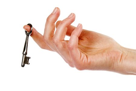 cliche: A concept image of a womans hand holding a key, dangling on one finger. Isolated on white with clipping mask.
