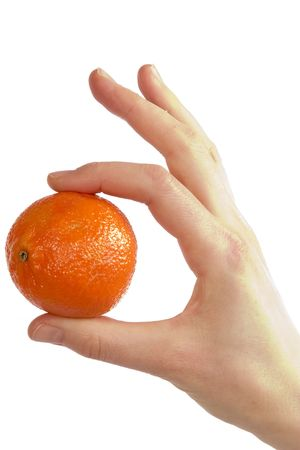 A womans hand holding a small christmas orange between her thunb and first finger. Isolated on white with . photo