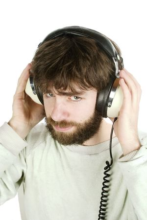 noise isolation: A young man looking sceptical while listening to music on headphones. Isolated on white with . Stock Photo