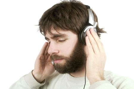 noise isolation: A young male with a beard listening to music on headphones. Isolated on white with .