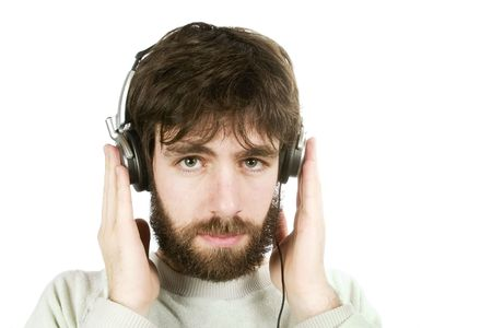 sceptical: A young man looking sceptical while listening to music on headphones. Isolated on white with . Stock Photo