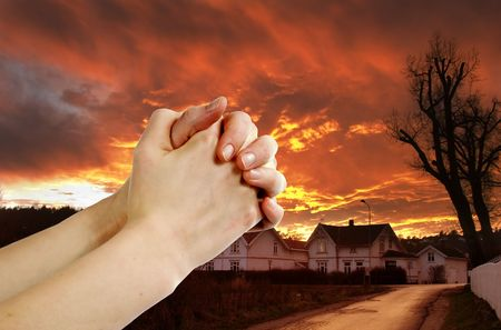 Hands praying with a dramatic red sky overa small town; prayer warr. Stock Photo - 342318