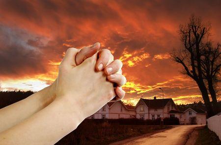 Manos orando con un espectacular cielo rojo overa pequeña ciudad; oración guerrero.  Foto de archivo - 342318