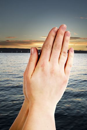 Praying hands with a landscape with the ocean and a sunset in the background photo