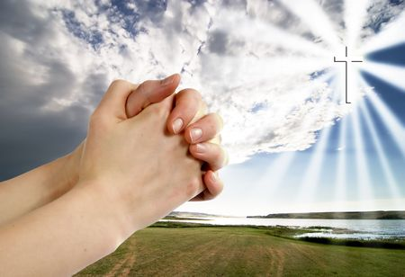 A pair of hands in a praying position set against a beautiful prairie lake landscape with a cross in the sky on the right side. photo