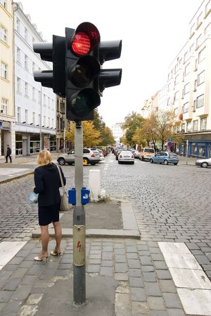 A woman standing by a red traffic light in Prague, Czech Republic. Stock Photo - 378831