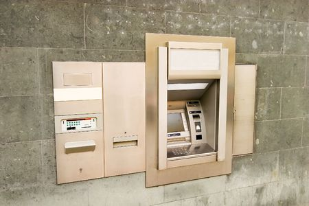 automatic teller: A bank machine on a stone wall.