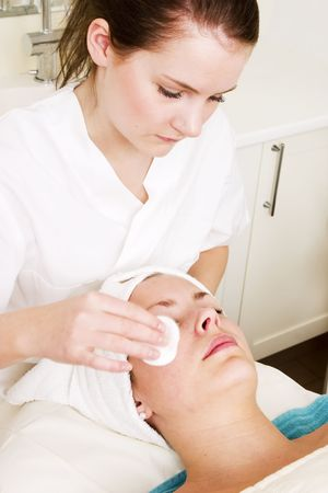 massaged: Lotion being massaged of the face at a beauty spa during a facial
