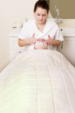 Lotion being massaged in during a facial at a beauty spa. Stock Photo - 378756