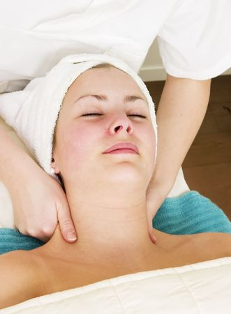 A woman receiving a facial and shoulder massage at a beauty spa. Stock Photo - 378669