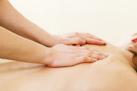back rub: A female receives a shoulder massage at a day spa.