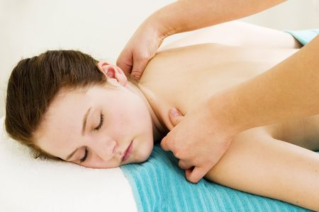 back rub: A close up image of a woman receiving a shoulder and back massage.