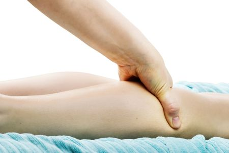 A detail image of a female leg being massaged. photo