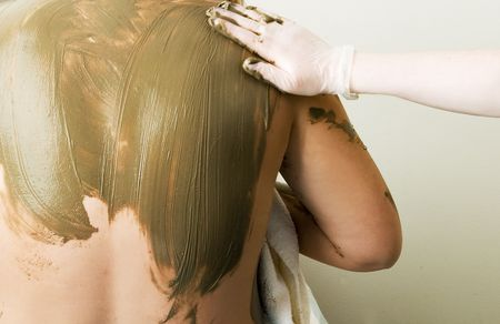 A sea mud full body wrap at a luxury spa being applied to the back and shoulders. photo