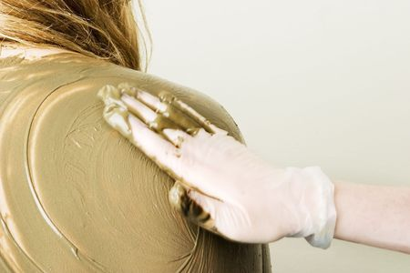A sea mud full body wrap at a luxury spa being applied to the back and shoulders with motion blur on the hand applying the mud. photo