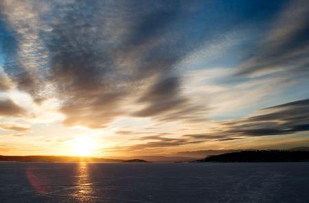 going down: Una puesta del sol de oro que va abajo detr�s de una colina sobre un lago congelado - fiordo. Fiordo de Oslo en marcha.