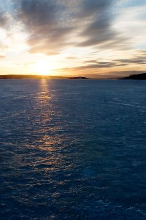A golden sunset going down behind a hill over a frozen lake - fjord.  Oslo fjord in March. Stock Photo - 774605